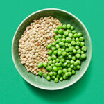 Bowl of peas and lentils on green background.
