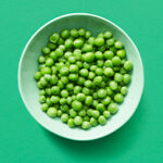 Bowl of peas on green background.