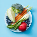 Plate of raw fruits and vegetables on blue background.