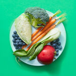 Plate of raw fruits and vegetables on green background.